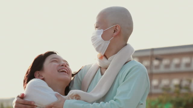 CU Mother wearing surgical mask hugging daughter (11-12) standing outdoors / Urayasu, Chiba, Japan