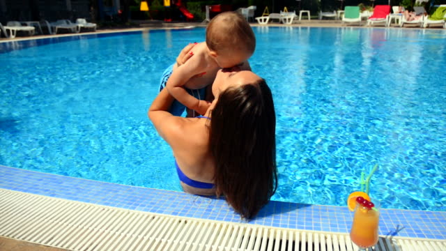 mother with baby boy in the pool