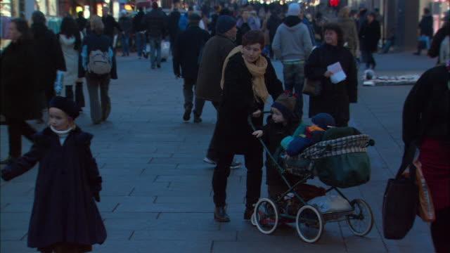 WS PAN Mother with children pushing pram in street / Oslo, Norway
