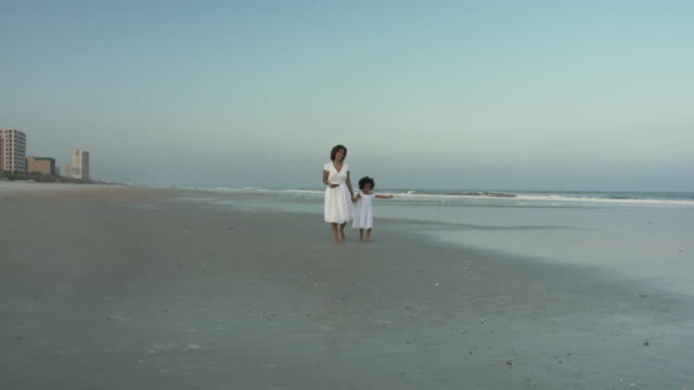 WS SLO MO Mother with daughter (4-5) walking on beach / Jacksonville, Florida, USA