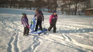 mother with little daughters and sleds in snow
