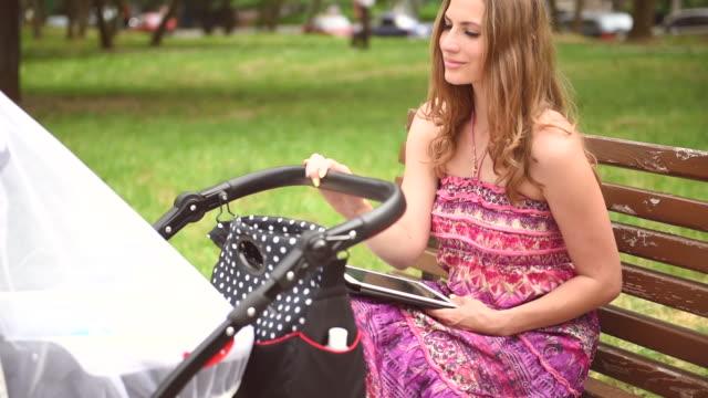Madre con un passeggino nel parco in una giornata di sole