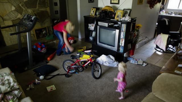 T/L WS HA Mother with two children in messy living room / Salt Lake City, Utah, USA