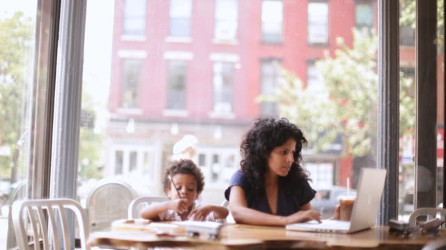HA Mother working on laptop at cafe table while son plays beside her / Brooklyn, New York, United States