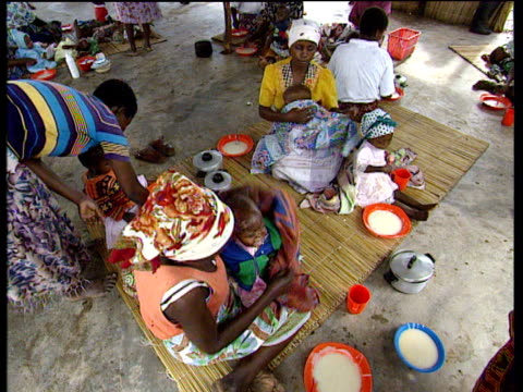 Mothers holding and feeding children at Chokwe feeding station after Mozambique Floods Jul 00