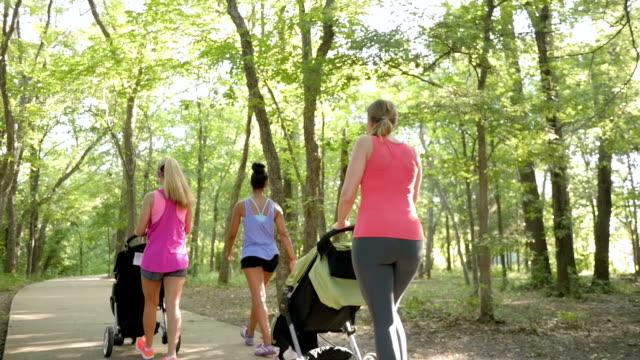 Mütter schieben Kinderwagen im running-club und im Gespräch mit Lehrer im park
