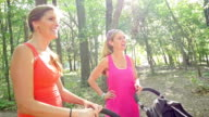 Mothers talking after exercising in park with jogging strollers