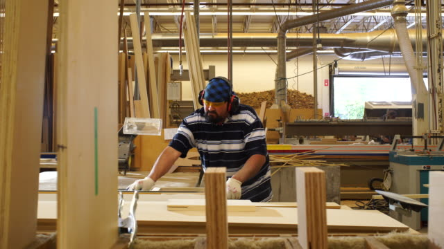 WS motion control dolly across vetical wood panels in foreground as worker assembles frames in custom woodworking shop