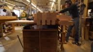 Motion-control, rising vertical crane move reveals worker power sanding cut wood pieces in woodworking shop