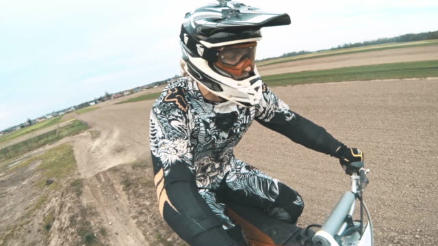 SLO MO POV Motocross biker riding on a dirt track