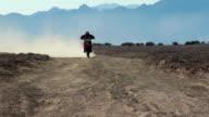 Motocross rider coming towards in desert
