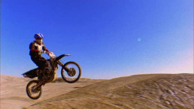 SM WS Motocross rider on motorcycle jumping off hill into mid air / Colorado, USA
