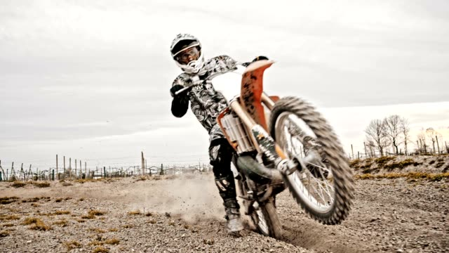 SLO MO Motocross rider riding through rutted turn