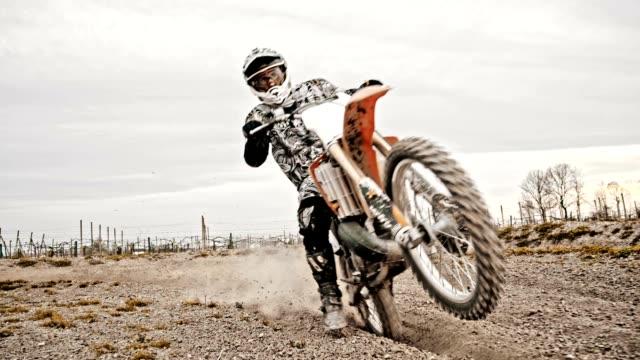 SLO MO Motocross rider rijden door rutted beurt