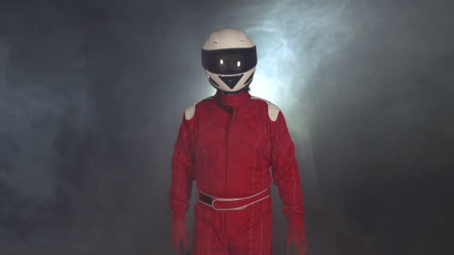 Motor racing / Formula One Driver walking through smoke with Helmet