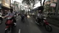 REAR POV WS Motorcycle Traffic Along Busy Street / Vietnam