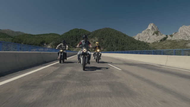 Motorcycles and bikers ridding over a road bridge