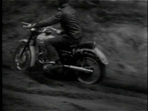 1958 DISTANCE SHOT Motorcyclist getting stuck in stand, then pulling bike out of hole by the back end / Lansing, Michigan, United States