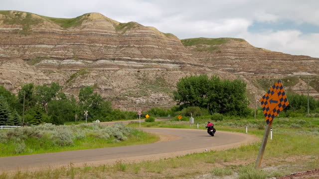 A motorcyclist passes on the road near the rock formations of Badlands
