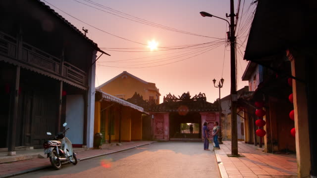Motorcyclists and pedestrians cross through a Japanese bridge in Hoi An, Vietnam at sunrise.