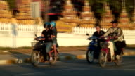 MS PAN Motorcyclists moving past Buddhist stupas / Vientiane, Laos