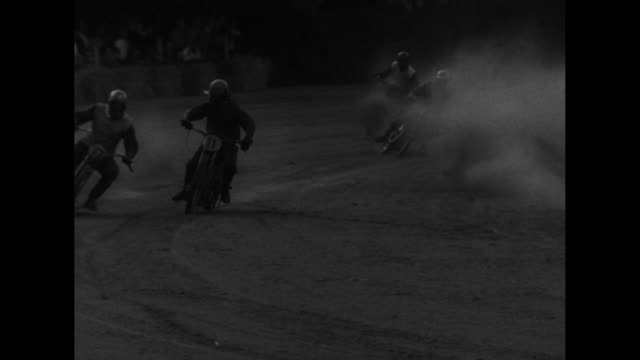 Motorcyclists speed down dusty track MS racers in goggles racing spewing dirt from back tires audience in stands man waves racers in audience...
