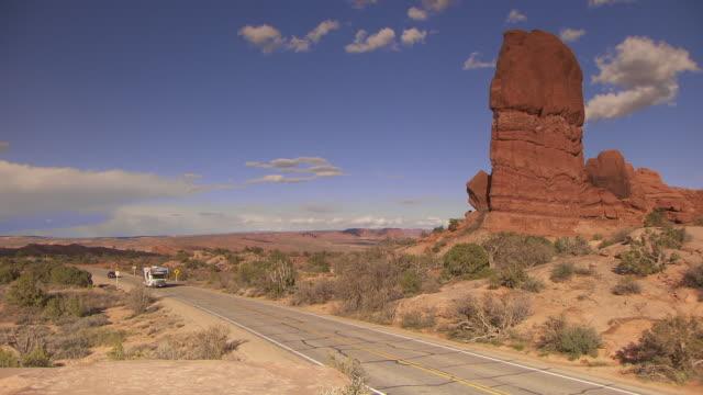 Motorhome RV driving through desert landscape -- pan to red rock desert