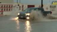 Motorists drive through high waters in a small Texas town as heavy rain continues to fall