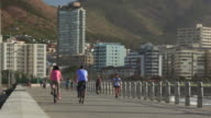 Moulle Point promenade with casual cyclists in front of Lion's Head and Signal Hill