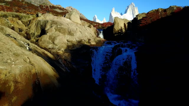 Mount Fitz Roy and the waterfall at dawn in the fall. Patagonia, Argentina