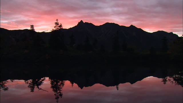 Mount Yarigatake rises in silhouette against a vivid pink sky.