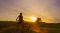 SLO MO Mountainbiker Radfahren bergauf bei Sonnenuntergang