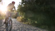 Mountain biker descends cobblestone path, sunrise