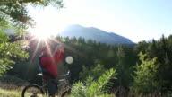 Mountain biker descends grassy ridgecrest, takes smart phone pic