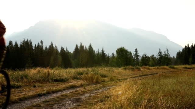 Mountain biker follows mountain track at sunrise