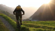 Mountain biker gains track above distant mountain ranges