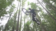 A mountain biker going off jumps in a forest on a mountain. - Super Slow Motion - filmed at 240 fps