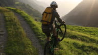 Mountain biker leaves track above distant mountain ranges