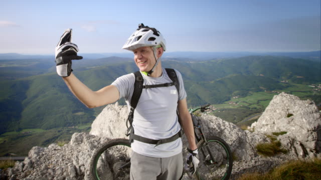 Mountain biker making video call as he reached the top