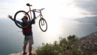Mountain biker on cliff above sea, raises bike overhead