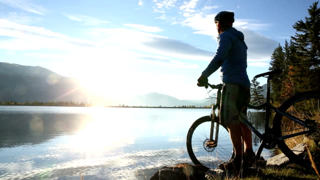 Mountain biker pushes bike to lake edge