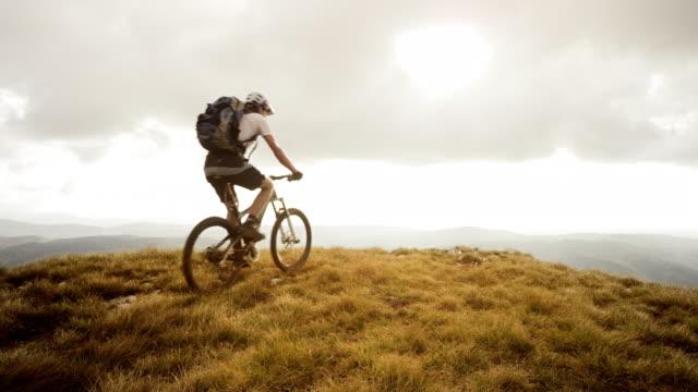 SLO MO mountainbiker bereiken van de top en het verhogen van de handen