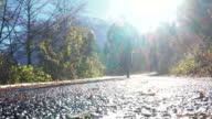 Mountain biker rides on wet road into sun