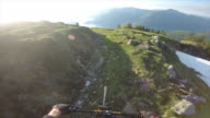 POV of mountain biker riding downhill trail at sunset