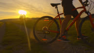 SLO MO Mountainbiker sein Fahrrad bei Sonnenuntergang