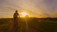 SLO MO Mountainbiker sein Fahrrad bergauf bei Sonnenuntergang