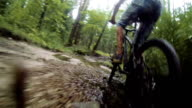 Mountain biker riding through a dirty puddle