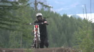 A mountain biker walking  his bike with a scenic forest in the background. - Super Slow Motion - filmed at 240 fps
