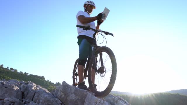 Mountainbiker mit digital-Tablette auf einem felsigen Hügel
