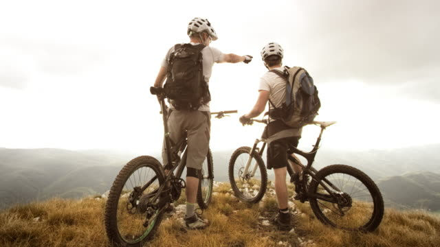 SLO MO mountain bikers admiring nature at edge of plateau